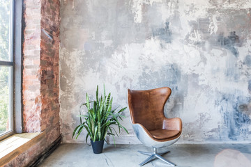 Chair in front of the grunge gray wall. Big window. Empty loft style room