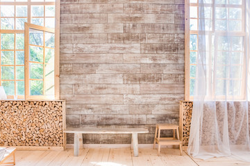 Scandinavian style sunny wooden interior. bench between windows and firewood storage