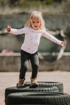 Happy joyful little girl having fun and walking through row of black car tires while playing outdoors on summer day