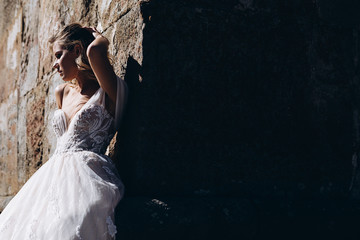 noise effect, selective focus: portrait of attractive bride hugging and kissing her groom while taking pictures in mountains