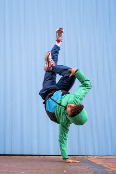 Cool curly male dancer in sportswear and sneakers doing handstands with cross legged against blue wall on street