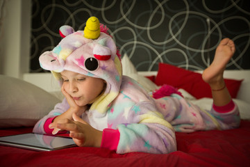 Girl using tablet on bed