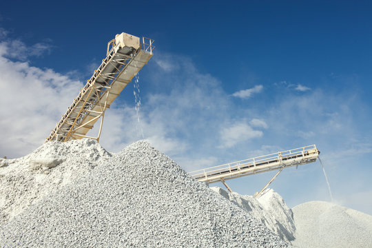 Conveyor belt at the equipment for crushing and sorting rocks into fractions at a mining enterprise on the background of the blue sky with clouds.