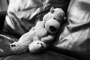 Soft toy bear on a leather sofa, black and white image