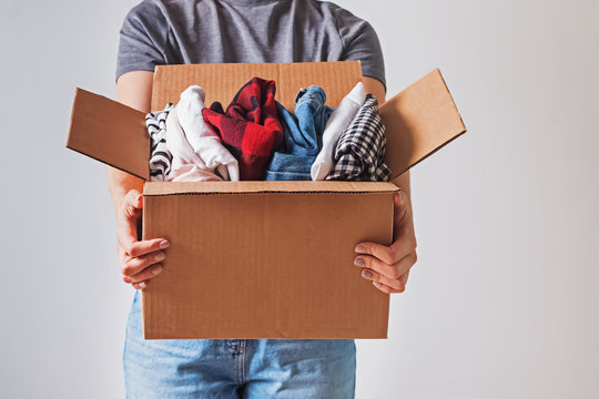 Unrecognizable woman holding box with clothes in it. close-up.