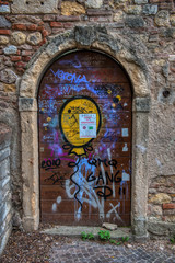 A pic of an old doorway with a steel door and graffiti all over it