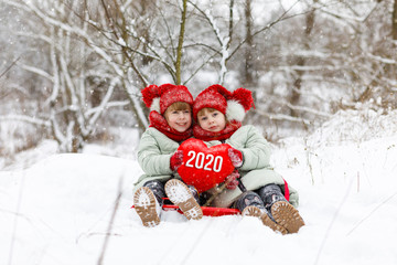 Twin sisters show heart with the numbers new 2020 year.