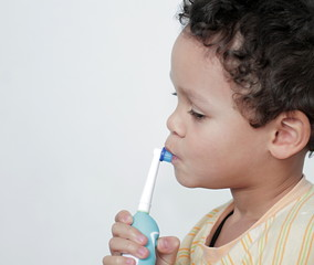 little boy brushing his teeth with an electric tooth brush stock image with grey background stock photo