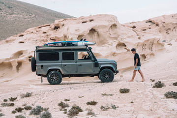 young man walking outside the 4x4 while camping