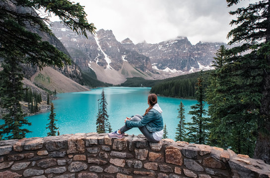 Woman sitting on rock wall looking towards Moraine Lake and mountains.