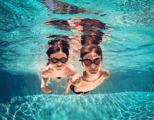 Underwater image of two boys swimming beside eachother in a pool.