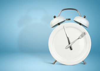 Concept of intermittent fasting, lunchtime, diet and weight loss. Plate as Alarm clock on blue