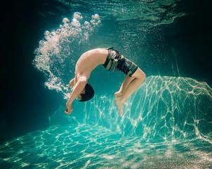 Underwater image of teenage boy doing a flip underwater.