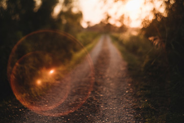 Sun Flare Bubble On Gravel Country Road  Leading to Sunset