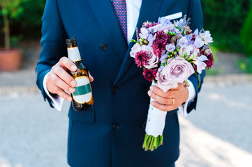 Groom holding bridal bouquet and grabbing  beer after wedding ceremony