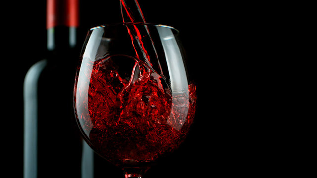 Detail of pouring red wine into glass