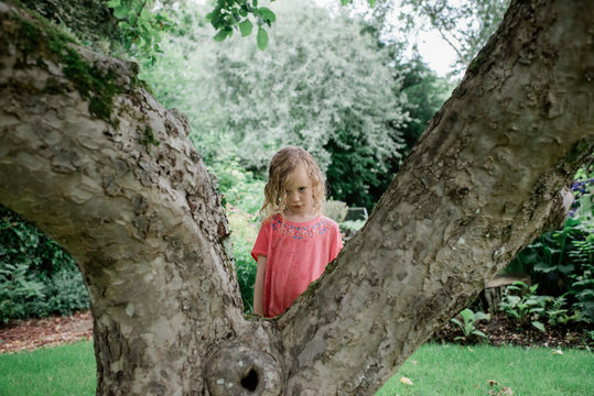 young girl looking sad stood behind a tree in the rain in summer