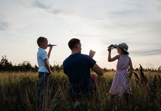 father playing paper aeroplanes with his son & daughter at sunset