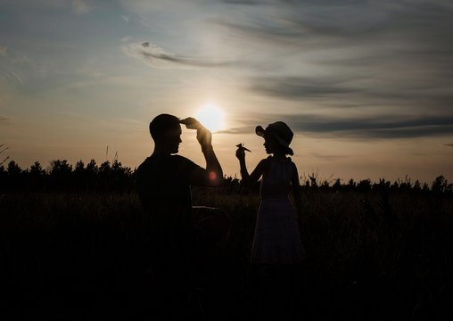 silhouette of father and daughter playing outside with paper aeroplane
