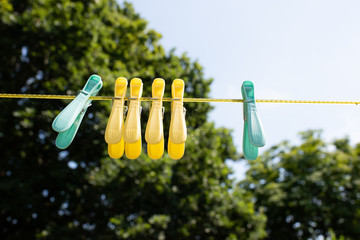 coloured pegs hanging on a washing line in an english country garden