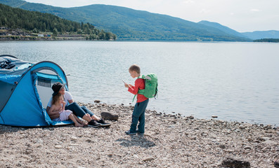 son taking pictures of mother and daughter camping at the beach