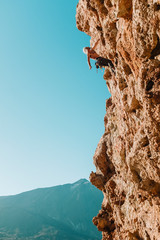 Pulled back view of male climber on wall with El Teide in the back
