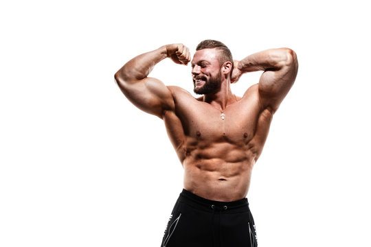 Smiling athletic caucasian man with a naked torso demonstrates biceps isolated on a white background.