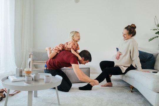 Man helping pregnant woman putting sock on