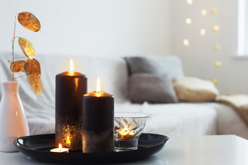 black and golden candles on white table