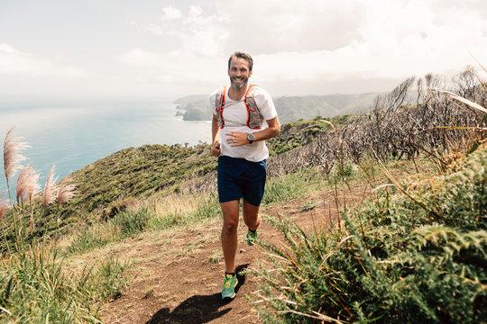 Smiling man running at coast