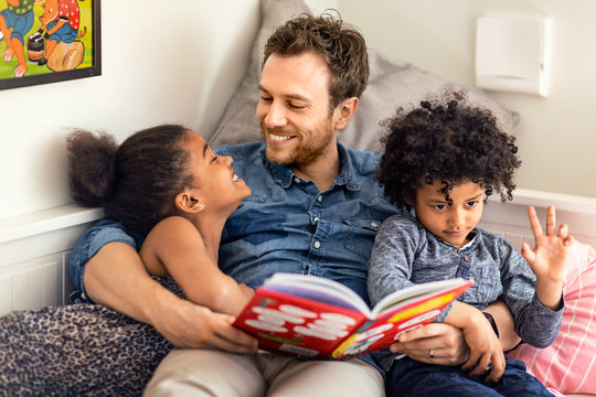 Father reading book to children at home
