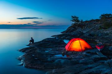 Man sitting by tent on coast