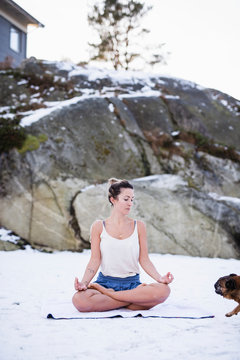 Young woman doing yoga in snow