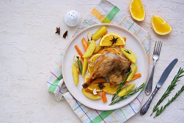 Roasted duck leg with potatoes, carrots and slices of orange on a ceramic plate on a light concrete background. Christmas and New Year dishes recipes. Duck recipes. French cuisine.