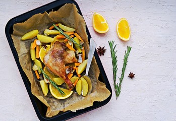Roasted duck leg with potatoes, carrots and slices of orange in a baking dish on a light concrete background. Christmas and New Year dishes recipes. Duck recipes. French cuisine.