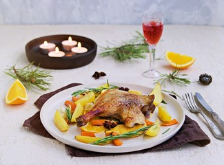 Roasted duck leg with potatoes, carrots and slices of orange on a ceramic plate on a light concrete background. Christmas and New Year dishes recipes. Duck recipes. French cuisine
