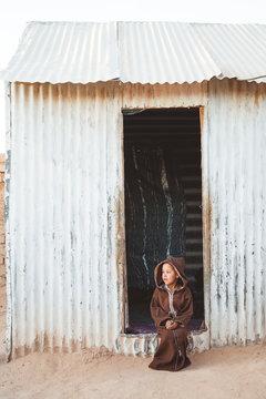 Ethnic kid sitting near shed