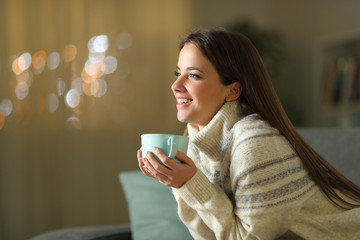 Happy woman holding coffee cup in winter at home