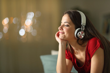 Relaxed woman listening to music at home in the night