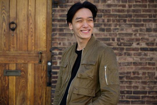 Man smiling outside brick house