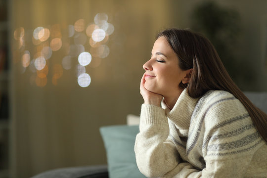 Relaxed woman meditating at home in the night in winter