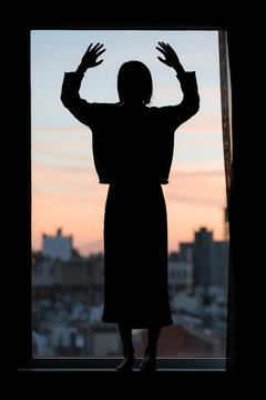 Silhouette of woman standing on window sill