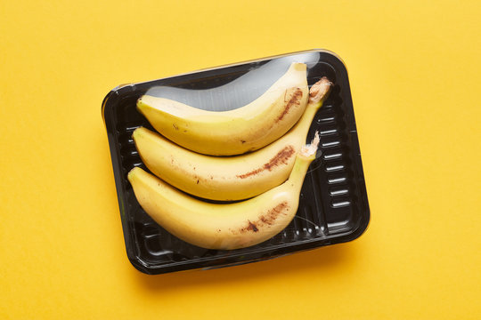Bananas in box with plastic wrap