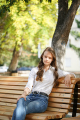 a girl in a white blouse and blue jeans sits on a wooden bench in autumn Park square, miss autumn