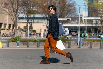 Young man with shopping bags walking on street