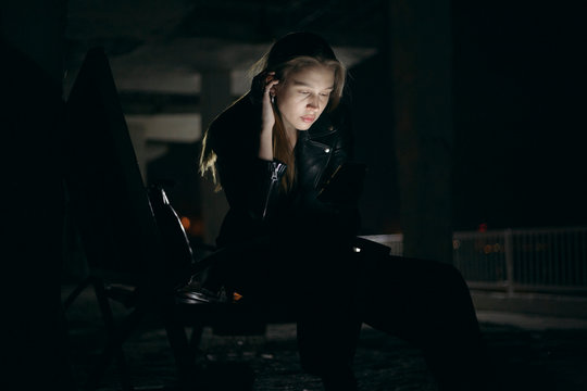 Young woman using smartphone on street at night