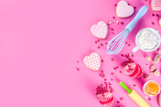 Valentine day cooking baking background. Utensils and ingredient for sweet Valentine cakes and heart shaped cookies, wooden background copy space