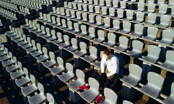 Sportsman resting on stadium seat