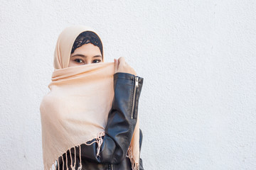 Portrait of beautiful iranian girl with blue eyes. Attractive muslim woman in hijab covering her face with scarf