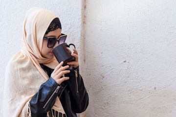 Pretty middle eastern girl in traditional Islamic clothing, drinking cup of coffee. Cute Arabian woman holding a cup of hot beverage in hands